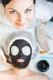 Professional woman, cosmetologist in spa salon applying mud face mask. She is happy and looking up at camera. Concept of beauty, healthy therapy, rejuvenation stock image