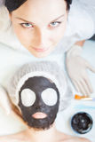 Professional woman, cosmetologist in spa salon applying mud face mask Royalty Free Stock Images