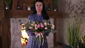 Professional woman floral artist, florist in blue dress perfoms the selfmade beautiful bouquet of different roses and. Leaves at workshop, flower shop or home stock video footage