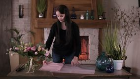 Professional woman floral artist, florist cutting packing paper on the table for bouquet at workshop, home studio. Floristry, handmade and small business stock video footage