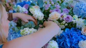 Florist making large floral basket with flowers at flower shop. Professional woman floral artist, florist making large floral basket with flowers at workshop stock images