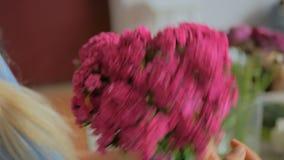 Professional florist preparing pink turkish carnation for bouquet at workshop. Professional woman floral artist, florist preparing flowers - pink turkish stock footage