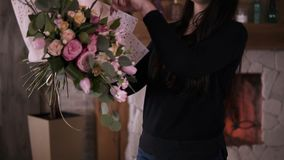 Professional woman floral artist, florist wraps flowers - pink roses in gift paper at workshop, home studio. Floristry. Handmade and small business concept stock video