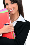 Professional woman with folders. Smiling young professional woman with multi-colored folders Royalty Free Stock Photo