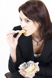 Professional woman having a bite. Dark haired woman in professional suit ona coffee break stock photo