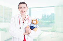 Professional woman medic holding teddy bear Stock Images
