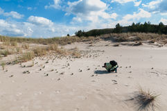 Professional woman photographer taking pictures on sand dune Royalty Free Stock Photography