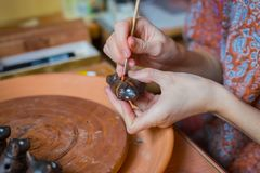 Professional woman potter painting ceramic souvenir penny whistle in pottery royalty free stock photos
