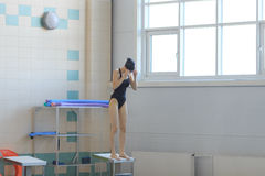 Professional woman swimmer in a starting position. Royalty Free Stock Photo