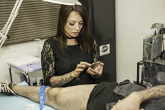 Professional woman tattooer with smartphone Stock Photography