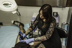 Professional woman tattooer working tattoo in a man leg. High an Stock Image