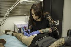 Professional woman tattooer working tattoo in a man leg. Royalty Free Stock Photo