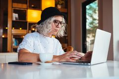Professional woman working on laptop computer and drinking coffee Royalty Free Stock Photos