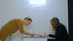 Professional women decorators working with kraft paper. Two professional women decorators, designers making envelopes at workshop, studio. Design, handmade and stock footage