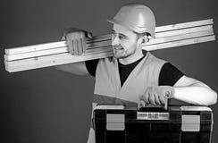 Professional woodworker concept. Man in helmet, hard hat holds toolbox and wooden beams, grey background. Carpenter. Labourer, builder, woodworker on smiling stock image
