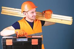 Professional woodworker concept. Man in helmet, hard hat holds toolbox and wooden beams, grey background. Carpenter. Labourer, builder, woodworker on smiling stock photography