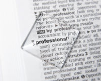 Professional. Word professional magnified in a dictionary stock photo