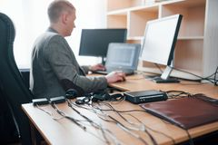 Professional is on the work. Polygraph examiner in the office with his lie detector`s equipment