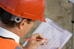 Professional Worker. A professional worker wearing safety equipment and reading plans for a new structure such as a Warehouse Stock Images