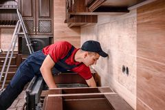 Professional worker assembling oven. Installation of kitchen furniture royalty free stock images