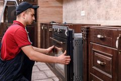 Professional worker assembling oven. Installation of kitchen furniture stock photo