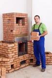 Professional worker building masonry heater. Carrying bricks Stock Photo