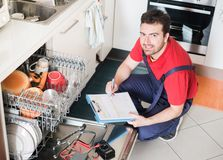 Worker estimating cost for broken dishwasher. Professional worker estimating cost for broken dishwasher Royalty Free Stock Images