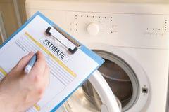 Worker estimating cost for broken washing machine. Professional worker estimating cost for broken washing machine Stock Photo