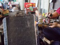 Professional worker with gas soldering radiator cooling of car in garage workshop Royalty Free Stock Photos
