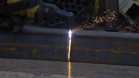 Gloved worker cuts a metal beam using a welding machine stock video footage