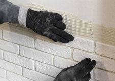 Professional worker gluing a tile on  wall Stock Photo