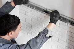 Professional worker gluing a tile on  wall Stock Photos