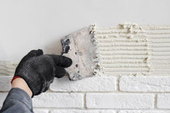 Professional worker gluing a tile on wall. Professional worker gluing decorative tile on wall stock image