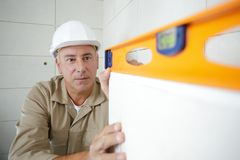 Professional worker in helmet measuring wall with level stock image