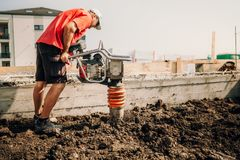 worker, industry details. Worker using vibratory compactor at house foundation stock images