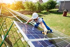 Professional worker installing solar panels on the green metal construction stock photo