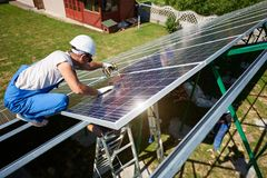 Professional worker installing solar panels on the green metal construction stock image