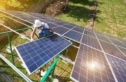 Professional worker installing solar panels on the green metal construction royalty free stock photos