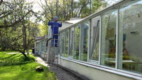 Professional worker on ladder washing glasshouse roof with high pressure tool. Garden cleaning services stock video footage