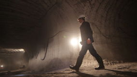 Professional worker with lantern walks along underground tunnel stock video