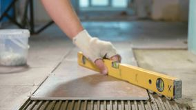 Professional worker laying tiles on floor. At construction site close-up slow motion. Builder using construction level for aligning tile Royalty Free Stock Photography