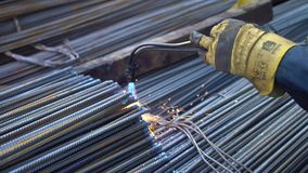 Professional worker processes metal rods with a flame of a welding machine in the territory of the metal base stock footage