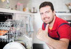 Worker repairing the dishwasher in the kitchen main focus on the hand. Professional worker repairing the dishwasher in the kitchen main focus on the hand Stock Photo