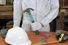 Professional worker with safety uniform holding hammer with other tools on wood workbench in carpentry workshop. Stock Image