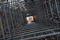 Professional workers seen through steel bars reinforcement on a construction site. Royalty Free Stock Images