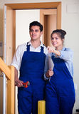 Professional workers with tools at doorway Royalty Free Stock Photos