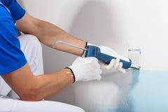 Professional Workman Applying Silicone Sealant With Caulking Gun Stock Photo
