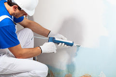 Professional Workman Applying Silicone Sealant With Caulking Gun. Close-up Of Professional Workman Applying Silicone Sealant With Caulking Gun on the Wall Stock Photo