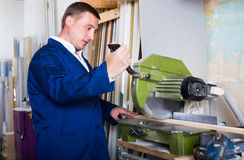 Professional workman cutting wooden planks using circular saw Royalty Free Stock Photo