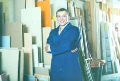 Professional workman standing with plywood pieces. In picture framing workshop Royalty Free Stock Images